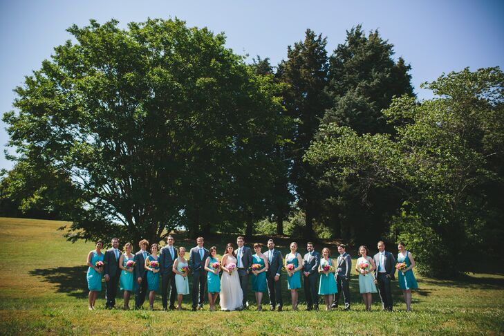 Jess, Dan and their wedding party stood outside, with a backdrop of the tall trees on the property. The wedding party matched one another with blue knee-length dresses and light blue ties under charcoal gray suits.