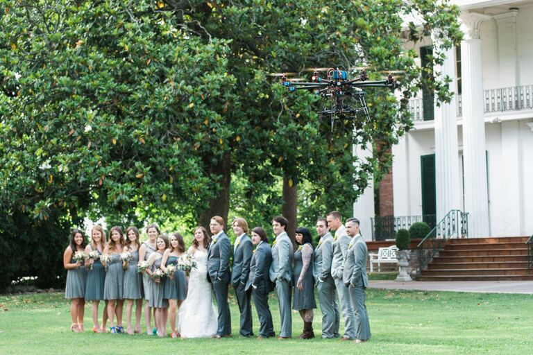 Wedding party smiling for the camera with a photography drone hovering above them