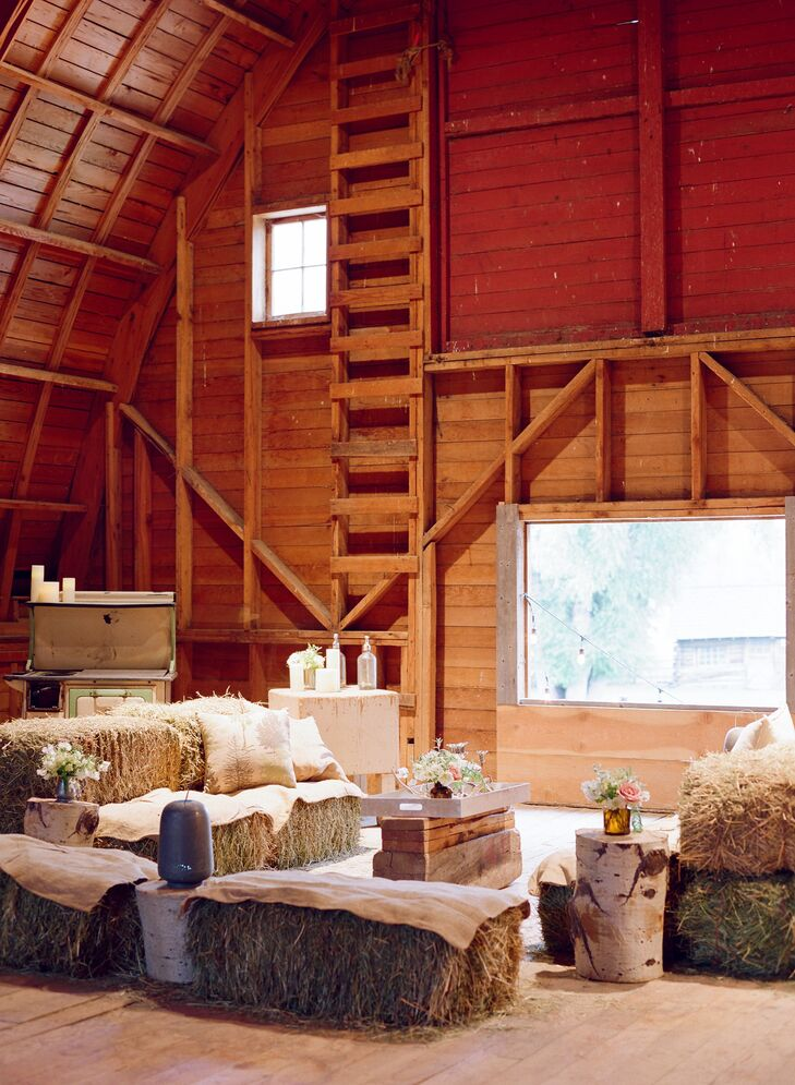 After the ceremony, guests walked along a path through the pastures to the old red barn for cocktail hour. The cocktail space featured a bar lit by antique chandeliers. Lounge spaces included hay bales and ranch furniture inside the barn and rustic pieces from Hunter Gatherer outside.