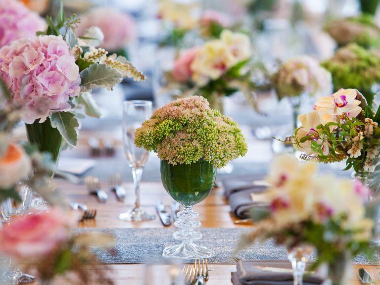 Wedding reception floral arrangements in colored glassware