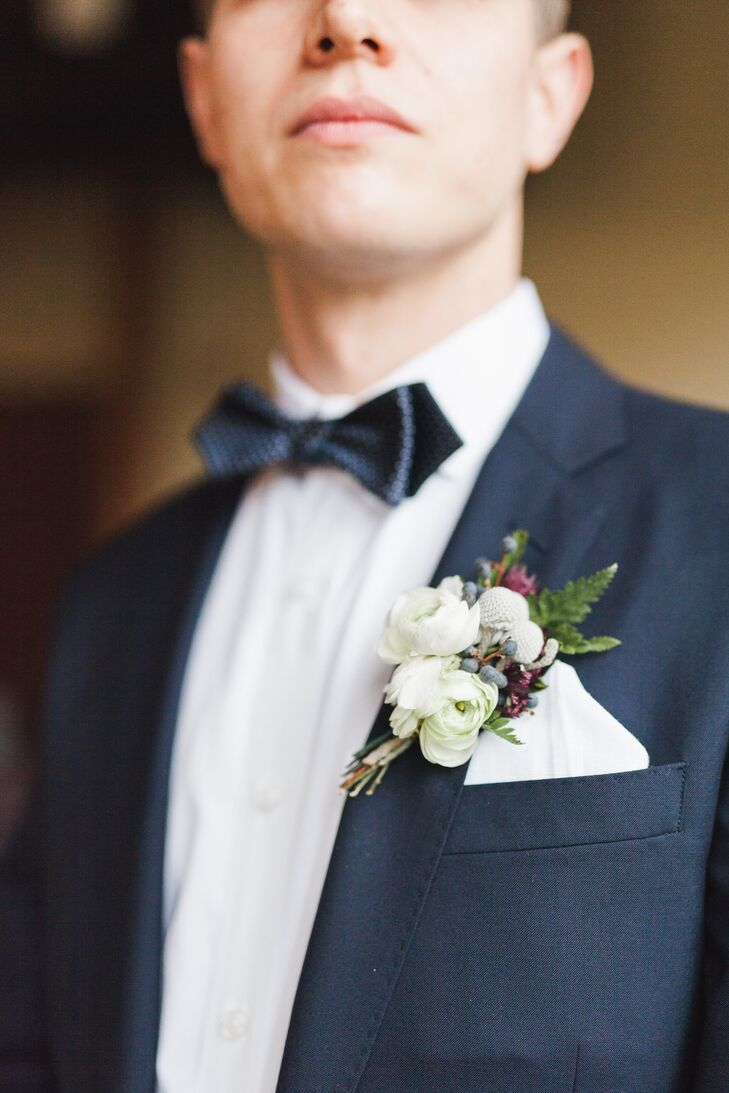 "To complete his dapper ""I do"" look, Benjamin jazzed up the lapel of his navy J.Crew suit with a fresh white ranunculus boutonniere trimmed with baby ferns, brunia and juniper berries."