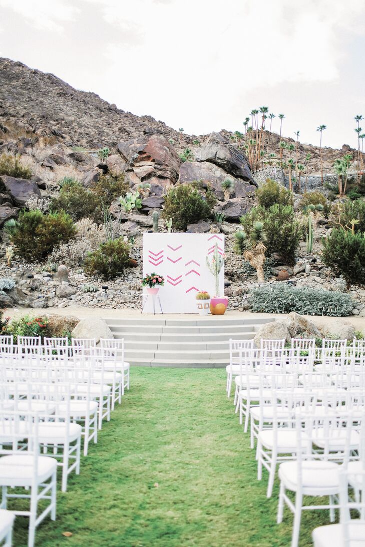With the rocky foothills of the San Jacinto Mountains behind them, Katie and Brian stood before a white wooden panel backdrop painted with pink sharrows (often seen on streets to mark bike lane). Here, they symbolized the couple's shared road together.