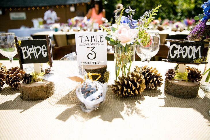 """Long dining tables were decorated with scattered pinecones, wooden slabs and moss that suited the natural surroundings. Tables were marked with black-and-white numbers, and Jennifer and Gregory sat at seats labeled with """"Bride"""" and """"Groom"""" signs."""