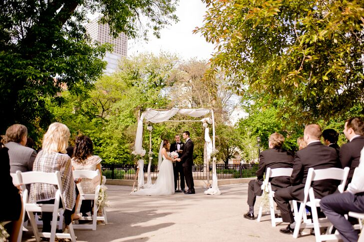 """Lindsay and Jacob exchanged vows under a wedding arch in Washington Square Park adorned with flowers. """"We chose to have our wedding in the city since we started our life together there,"""" the bride explains. """"We wanted each of our venues to represent our favorite parts of Chicago."""""""