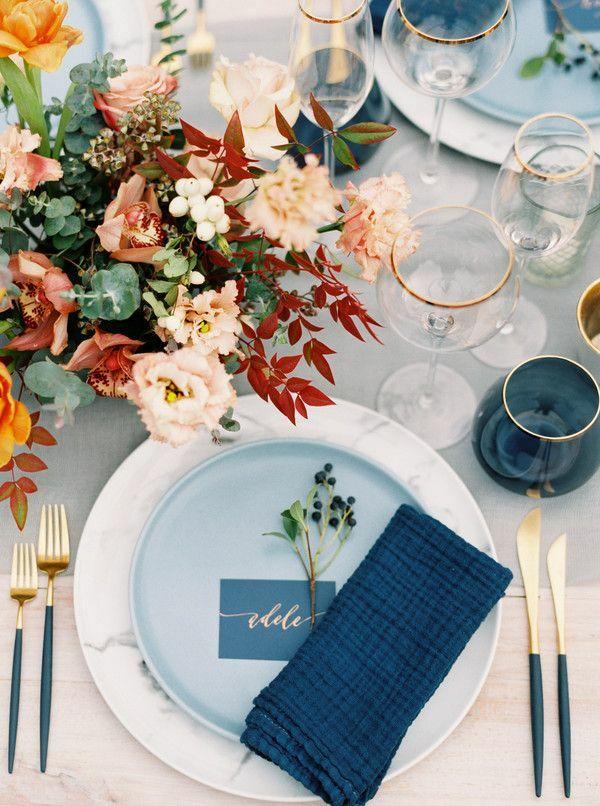 Brown floral arrangement beside blue place setting