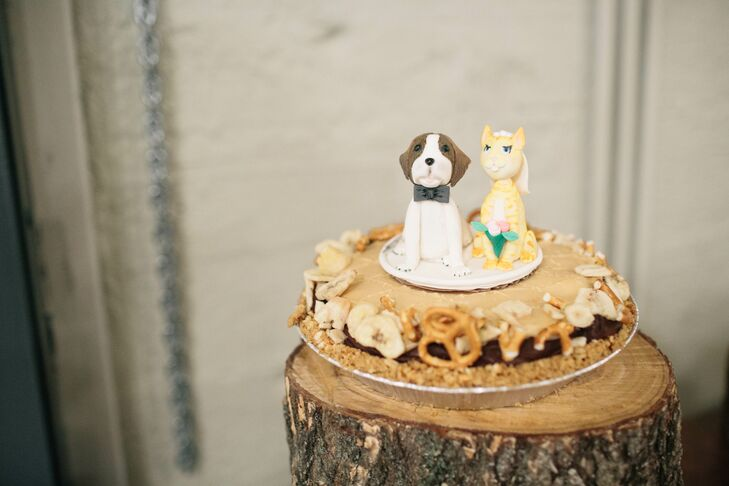 """""""I was lucky enough to have so many talented friends who contributed to our wedding in amazing ways,"""" the bride says. """"A friend from college has a cake-making business and made us a Saint Bernard and orange cat cake topper that paid homage to our cat, Chuck. They sat on top of a Fat Elvis pie and it was so 'us'."""""""