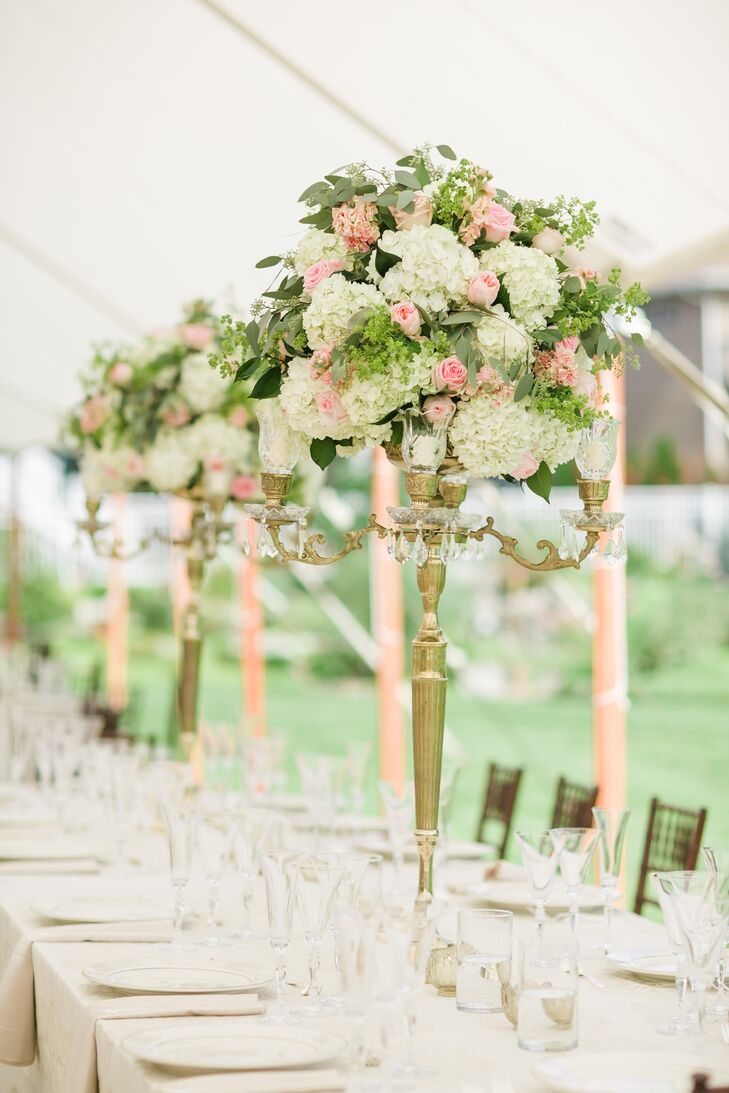 Tall gold candelabras were filled with a lush assortment of ivory hydrangeas and pink roses accented with greens.