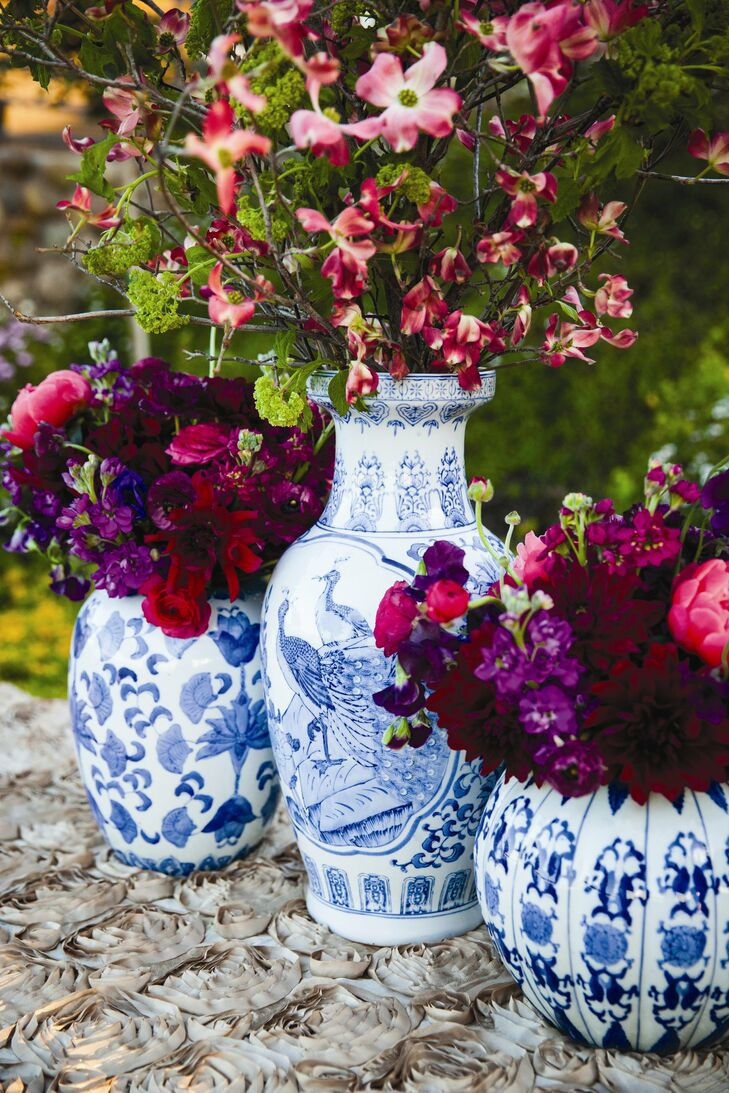 Large arrangements of fuchsia and purple flowers were placed in classic blue willow Chinese vases, adding color and sophistication to the decor.