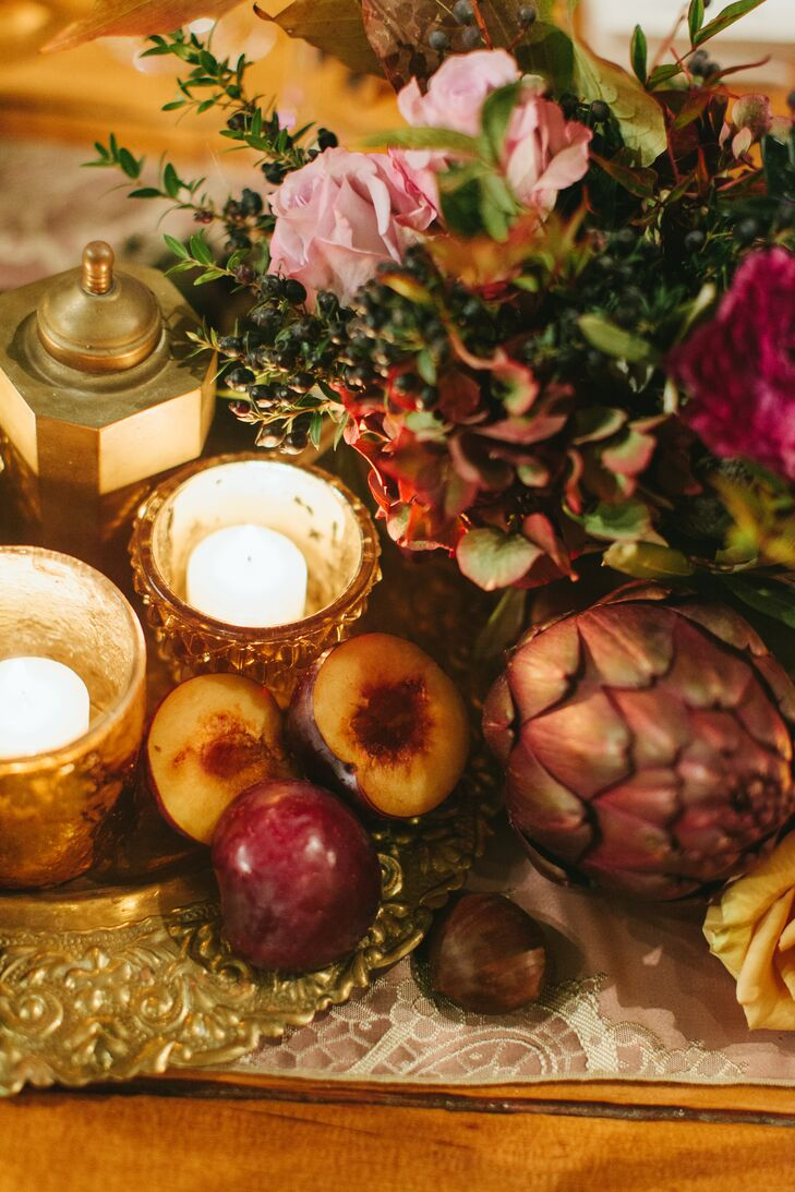 With an autumn wedding in the works, Rachel and John wanted the decor to capture the essence of the season. The couple envisioned centerpieces and tablescapes that incorporated elements from still life paintings like gilded accents, warm candlelight and an assortment of seasonal fruits. Flowers by Semia transformed their vision into reality, creating textured arrangements with succulents, artichokes, acorns, fruits and lots of richly hued foliage, which played up the venue's rustic, vintage feel.