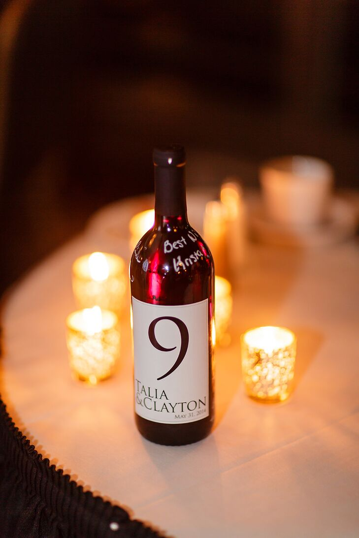 Instead of the usual placards, Talia and Clayton used customized wine bottles that were labeled with their names for the table numbers.