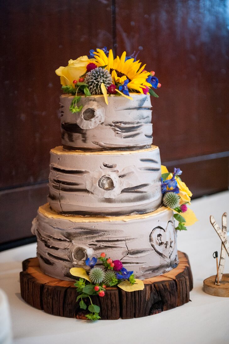 "Kimberly and Charles enjoyed a three-tier wedding cake from Whole Foods in Colorado Springs. ""We chose one of their most popular kinds—the berry chantilly whipped vanilla buttercream cake,"" Kimberly says. ""As for its design, we chose a custom-made Aspen tree with our initials carved into a heart on the side."""