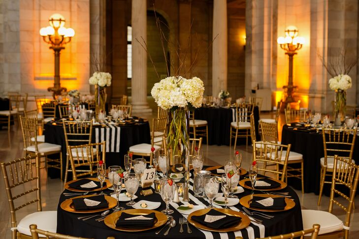 Black and white striped table runners draped over the black tablecloth on the dining table, which was set with gold plates and black napkins. A tall centerpiece of ivory hydrangeas stood in the middle of the table.
