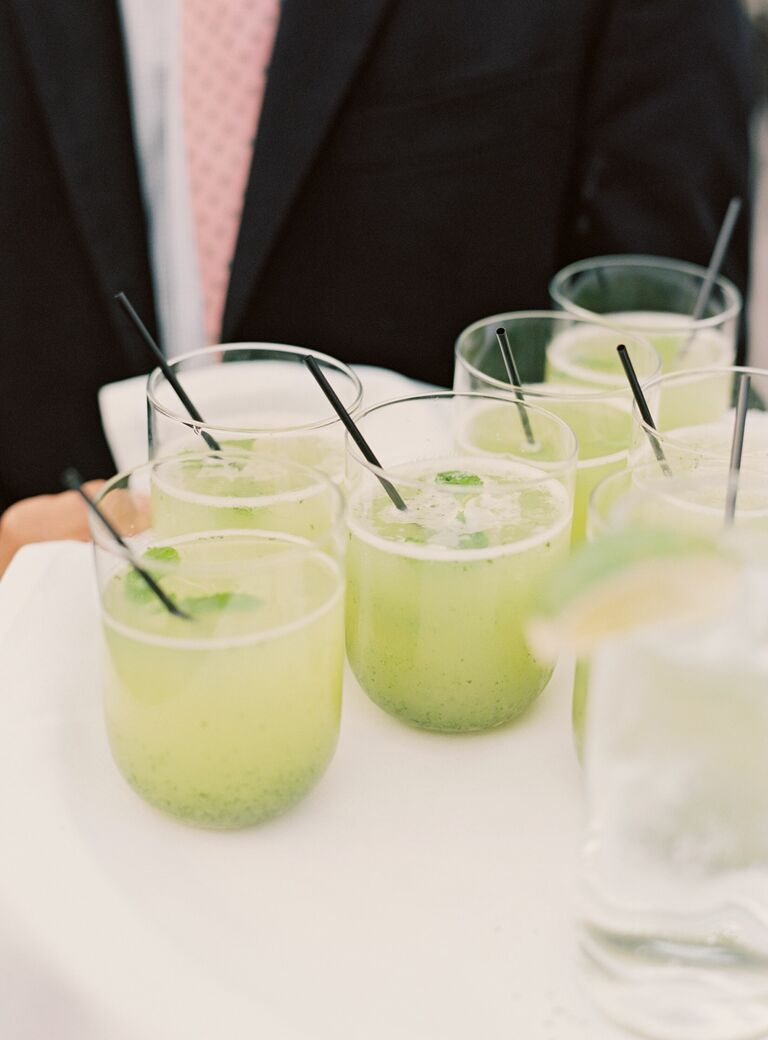 waiter serving green cocktails mojitos in stemless glasses with straws