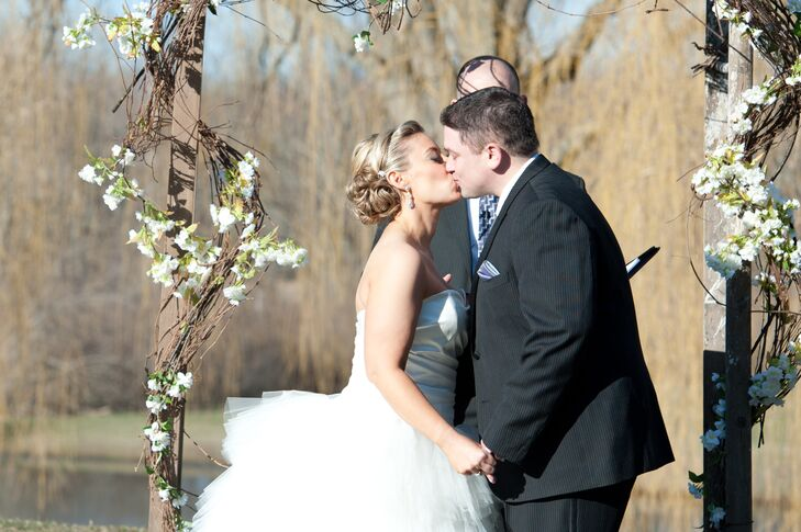 Bride, Groom Kiss During Outdoor Ceremony