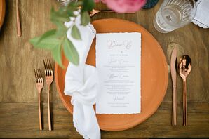 Elegant Place Setting with Orange Dinnerware, Gold Flatware and Menu
