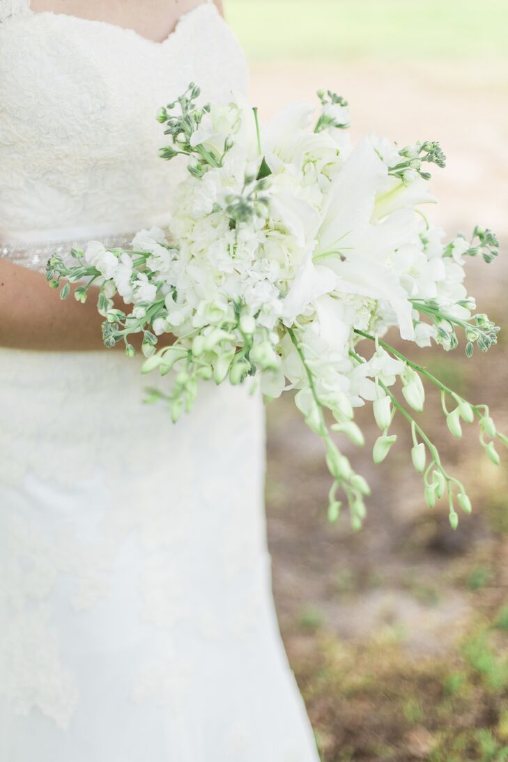 Cami picked up on their venue's scenery and chose a natural bouquet. White delphiniums cascaded from the arrangement as a bolder stargazer lily stood out at the center.