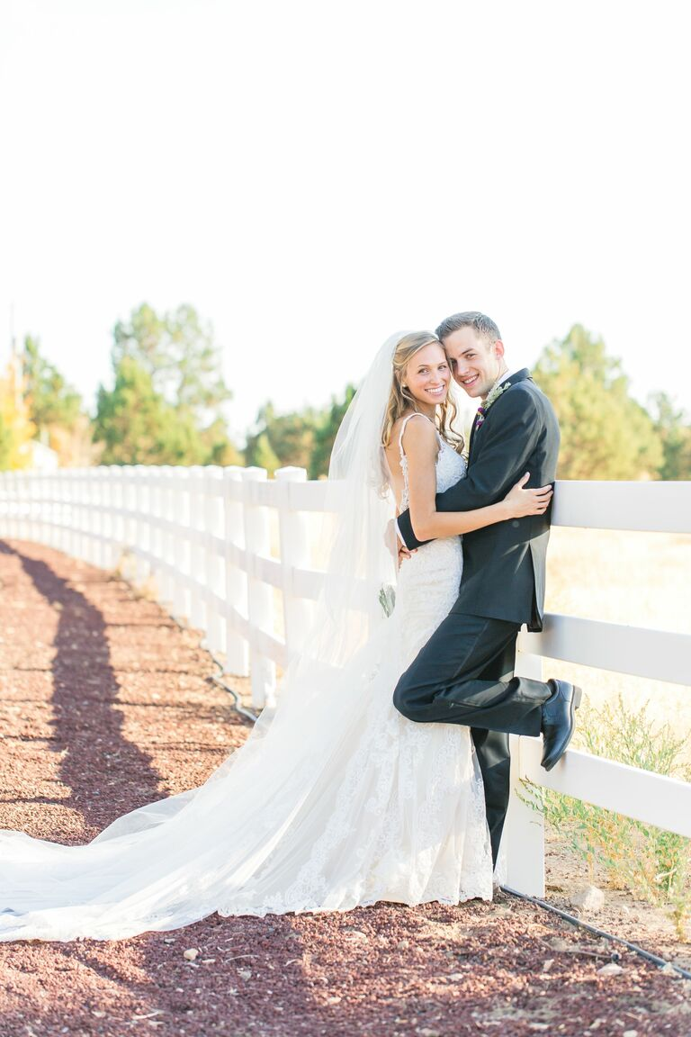 bride and groom posing by white fence