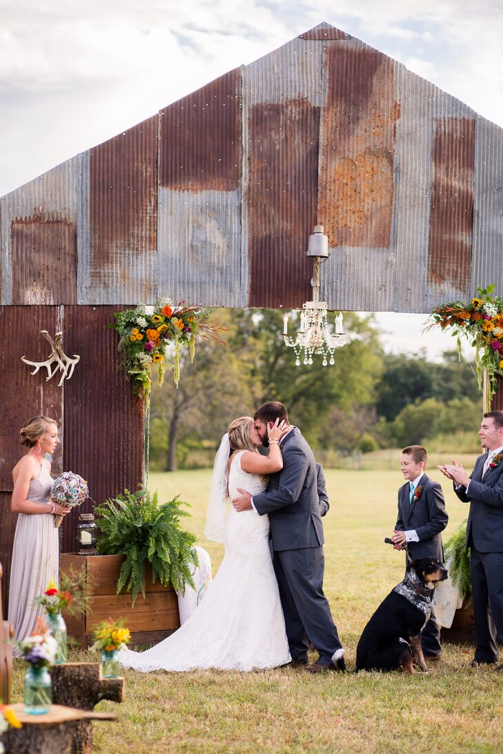 First Kiss in Front of Rustic Backdrop