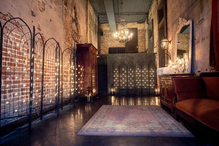 """Taking inspiration from their venue, Latrobe's on Royal in New Orleans, Louisiana, their entrance was lined with these chic iron arches covered with tiered tealight candles. Each one added a soft glow against the exposed bright walls and vintage decor. """"It looked amazing against the window and rustic mirrors,"""" Kendra says."""