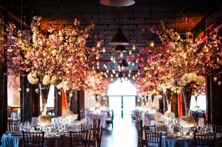 "Growing up, Hayley had a cherry tree that would brighten up her backyard with beautiful pink blooms every spring. Knowing that cherry blossoms would be in bloom at the time of the wedding, the bride-to-be envisioned the reception as a breathtaking floral forest filled with the pretty petals. Louis Konstantinos Floral Decor took her vision and ran with it, creating dozens of skyward reaching arrangements of cherry blooms and white hydrangeas, the lush centerpieces punctuated with hanging candles that added a note of romance and ambiance. ""My jaw dropped when I saw the room,"" says Hayley. ""The room just felt magical and I think our guests were in awe."""