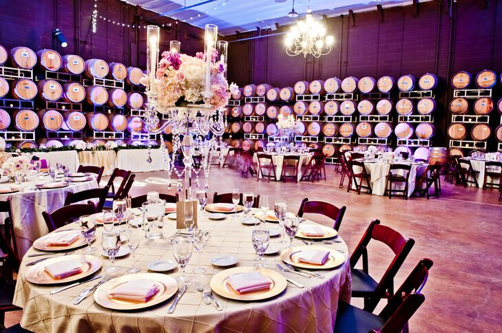 Inside the barrel room, round dining tables dressed in champagne-colored linens were decorated with tall glass candelabras, with lush flower arrangements and candles displayed on top.