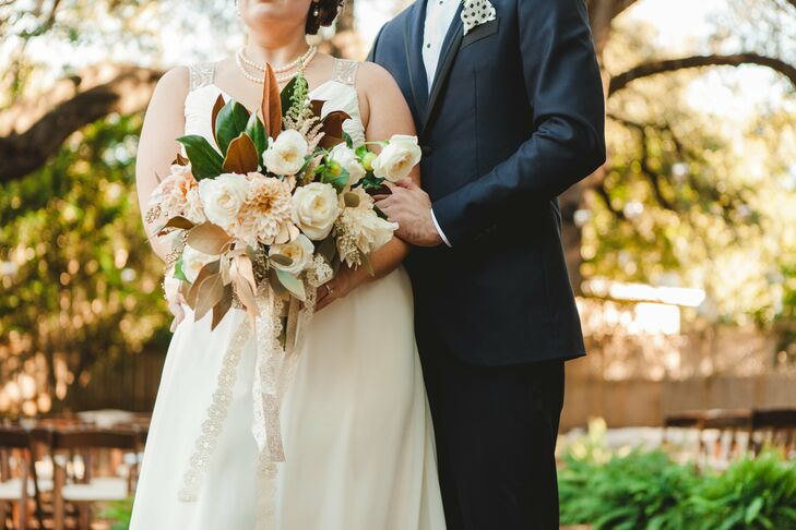 Sara's lush bridal bouquet was filled with ivory garden roses, dahlias and astilbe. Tropical foliage added a unique look and a layer of depth to the bouquet.