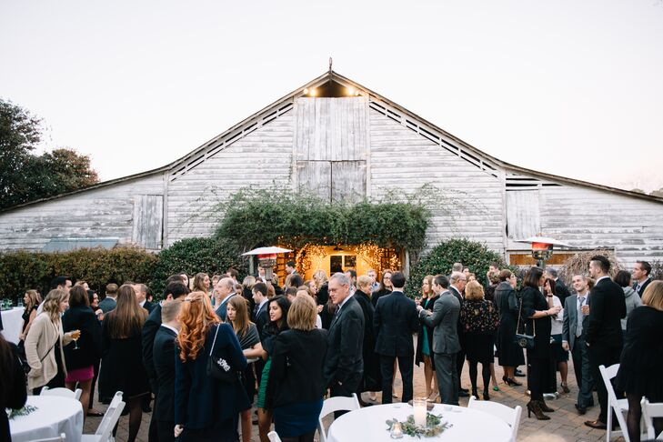 Kara and Pat had their cocktail hour outside the rustic white barn. They served drinks and had tables decorated with seeded eucalyptus and pillar candles. Guests mingled in the gorgeous November weather before heading inside for barbecue and dancing.