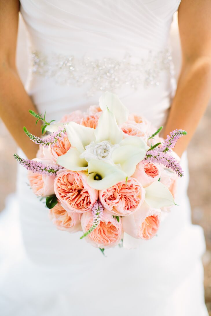 """""""My bouquet included stunning coral garden roses, white calla lilies accented with dusty miller,"""" says Brittney. """"It included a personal touch with my great grandmother's diamond necklace wrapped into the flowers."""""""