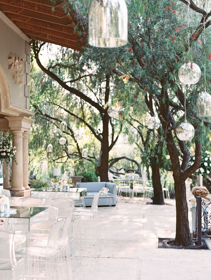 At the romantic, modern reception under the trees at Monique's family home in Tegucigalpa, Honduras, guests lounged on gray-blue furniture under clear rounded lanterns.