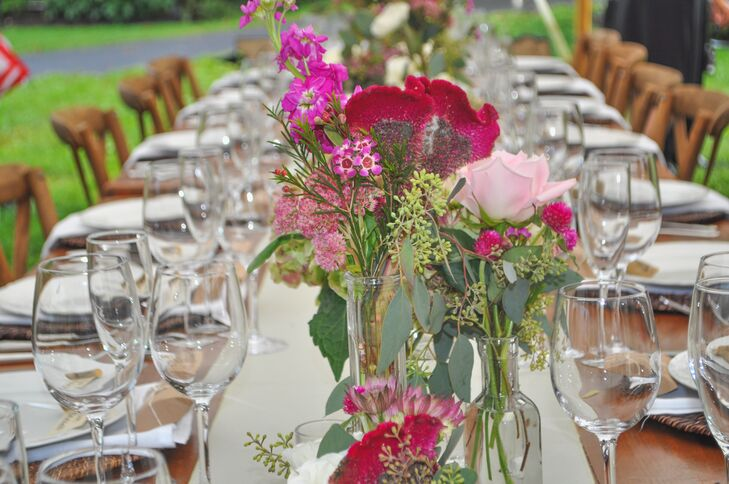"""""""Under the tent, farmhouse tables with celadon green runners, white china on rattan chargers, cross-back chairs,  candlelight and lots of small flower arrangements in vintage glass bottle and mason jars,"""" Karen says."""
