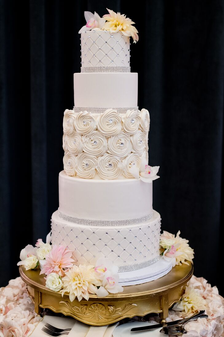 The cake's five tiers had different designs, including an iced rose center layer. It was vanilla cake with Italian buttercream frosting and fresh strawberry compote filling.