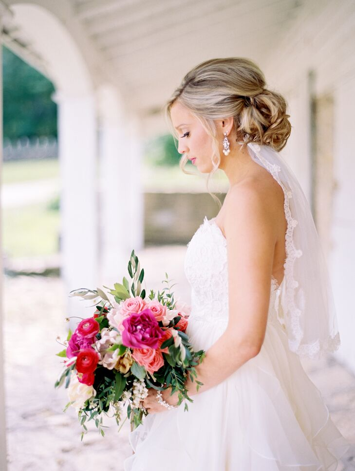"""For a classic, romantic look, Kristina wore her hair up in a low, loosely curled updo, adding a lace-trimmed veil for a finishing touch. """"When I first started looking for a gown, I tried on my mother's, which my grandmother made by hand,"""" says Kristina. """"It was a beautiful dress, but not quite the style I was going for. Luckily, my grandmother had made a matching headpiece that had a removable veil. I could just pin it right into my hair and the lace detailing matched my gown."""""""