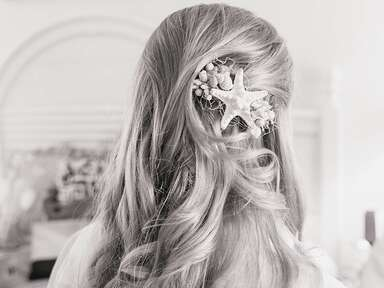 Beach wedding hairstyle with loose curls and a starfish hairpiece