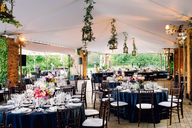 "Guests gathered under the canopy of McGinley Pavilion for the reception. ""We wanted to keep the décor simple yet elegant and let the centerpieces and the beauty of the garden take center stage,"" Erin says."