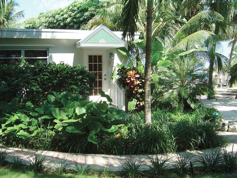 One story white bungalow at Kona Kai Resort with green trim with palm trees and lush foliage