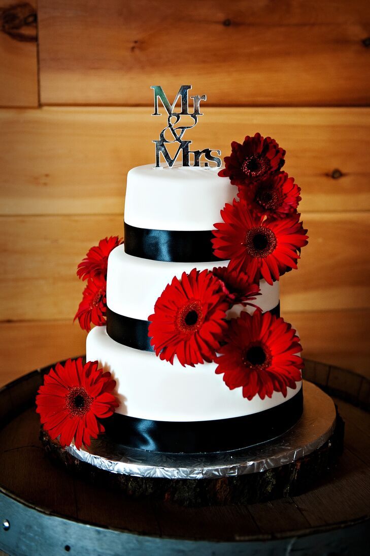 Large, red gerbera daisies cascaded down the sides of the three-tier white cake. Black satin ribbons were wrapped at the base of each layer.