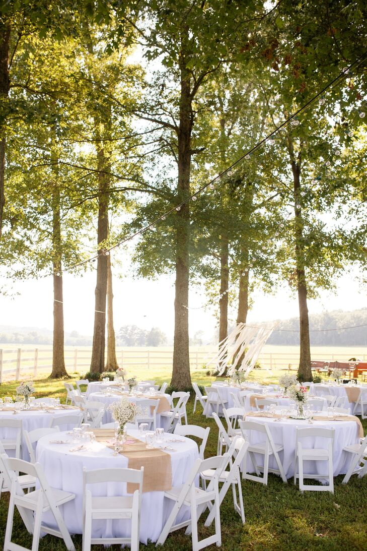 Hosting the wedding at Alix's grandfather's farm could not have been a more fitting choice for the couple's laid-back, rustic theme. They hosted the affair outdoors, setting up the reception tables out on the sprawling lawn underneath tall majestic trees dotted with lush foliage. The setting felt intimate and relaxed, with the natural landscape providing a breathtaking backdrop for the evening.