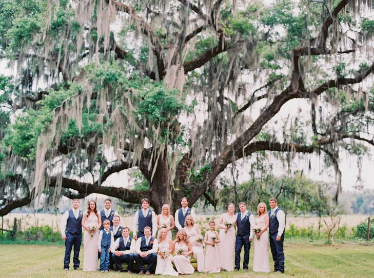 """The groomsmen were dressed in casual Lucky Brand Jeans, cowboy boots, white shirts, blue vests and yellow craspedia boutonnieres. Greg and two groomsmen stood out with custom """"Stone"""" engraved belt buckles. The bridesmaids wore champagne floor-length dresses."""