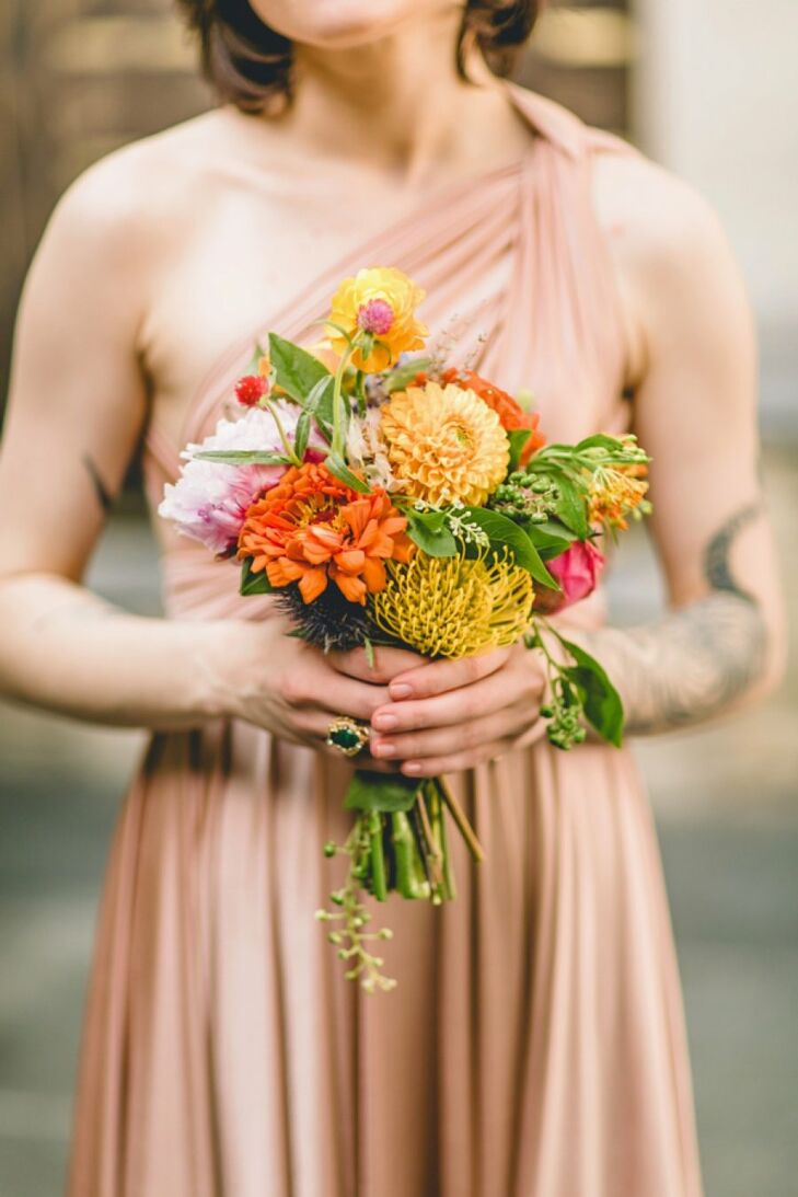 Colorful bouquets of zinnias, dahlias, pincushion proteas and ranunculus added a splash of color to the bridesmaids' ensembles.