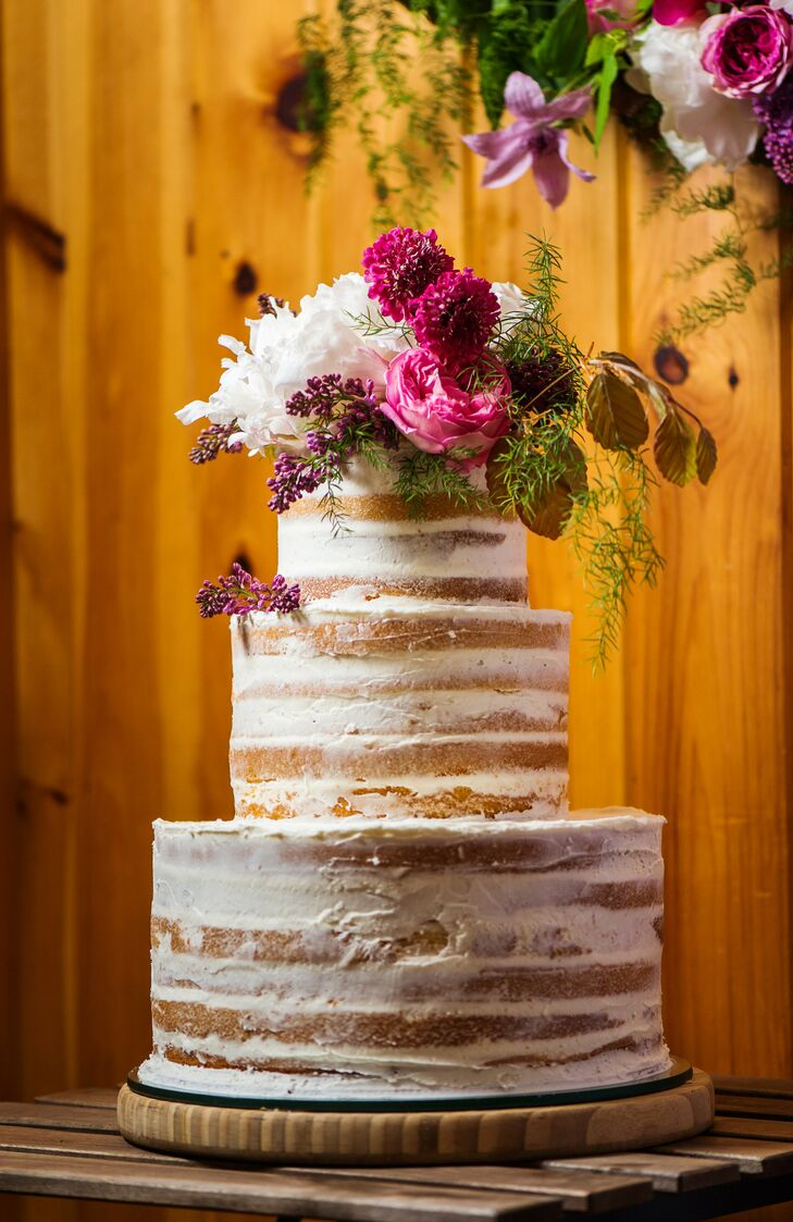 After a dinner of halibut and duck, guests were treated to a piece of wedding cake. Pastry chef Charity Church of the Migis Lodge drew inspiration from the wedding's rustic vibe and whipped up a naked three-tier confection with light lemon cake and buttercream frosting. To tie into the rest of the decor, the cake was topped with a bunch of bright purple, pink and white dahlias, roses and peonies.