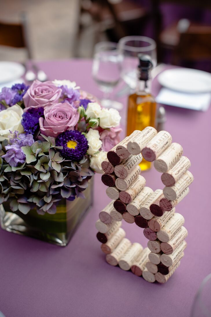 Numbers made from Jacuzzi Family Vineyards's wine corks marked dining tables, incorporating the wine-country style into the wedding day. Lush flower centerpieces filled with roses, hydrangeas and other purple blooms decorated the dining tables as well, adding more purple color to the occasion.