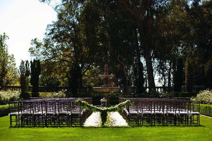 The ceremony took place on the grounds of Greystone Estate, facing an impressive stone fountain. The aisle was covered in white rose petals for an ethereal touch.