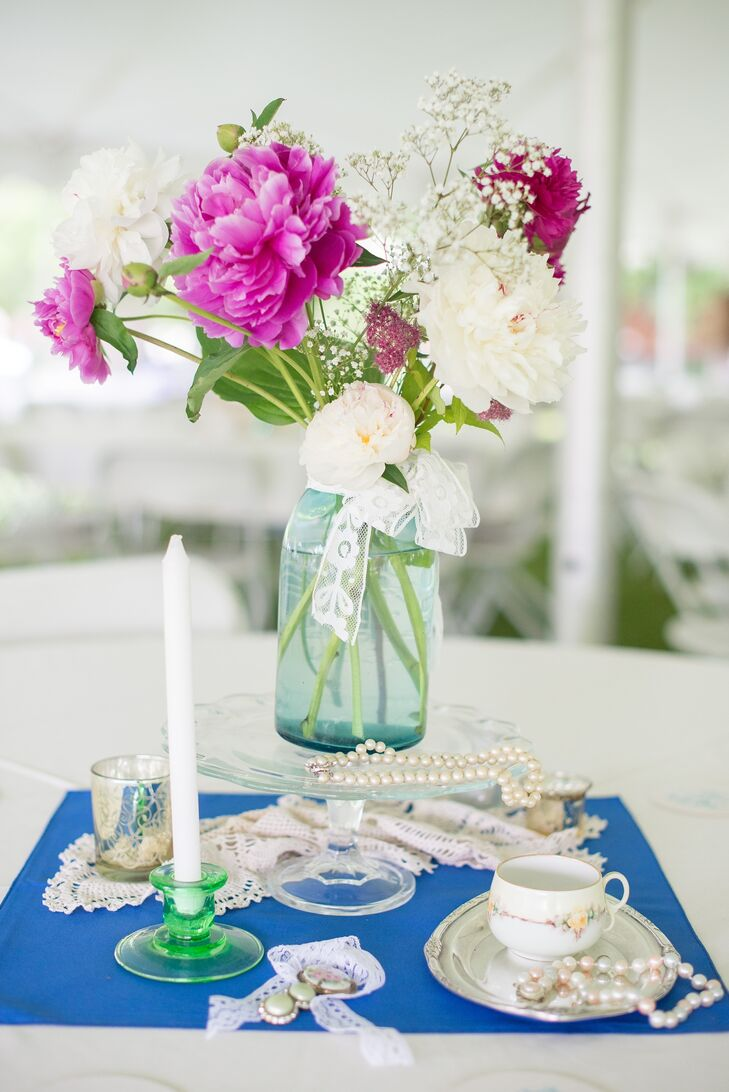 The table centerpieces included peonies in blue mason jars and collections of vintage jewels, mirrors and other antique finds.