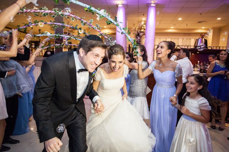 Emma and Michael planned the entire wedding themselves and even had time to DIY some of their decor. They made their entrance under an archway of daisies and ivy held by their guests as bubbles blew all over the place.
