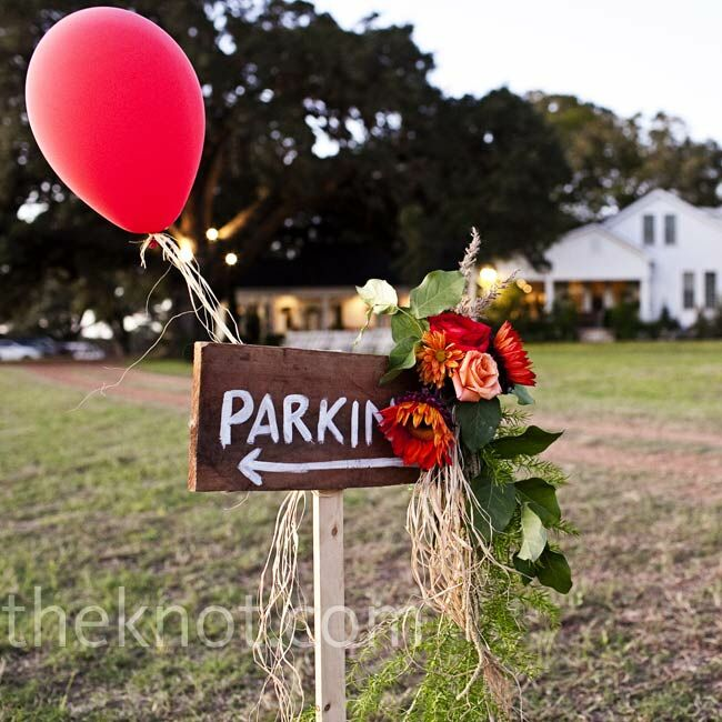 Red gerbera daisies and peach roses decorated the signs that directed guests where to park.