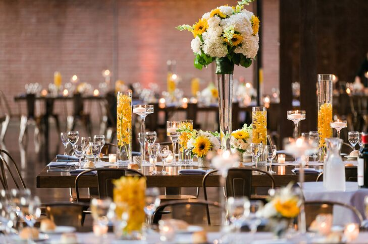 To play into the venue's unique industrial vibe while highlighting the summer season, Alyse and Vadim topped their rustic farm tables with a mix of modern and classic centerpieces in brilliant shades of yellow and white. Lush bunches of hydrangeas, stock, orchids and sunflowers were piled high atop glass trumpet vases and orchids floated serenely in hurricane vessels. Dozens of floating and votive candles cast a warm, ambient glow over the room, adding an air of romance to the space.