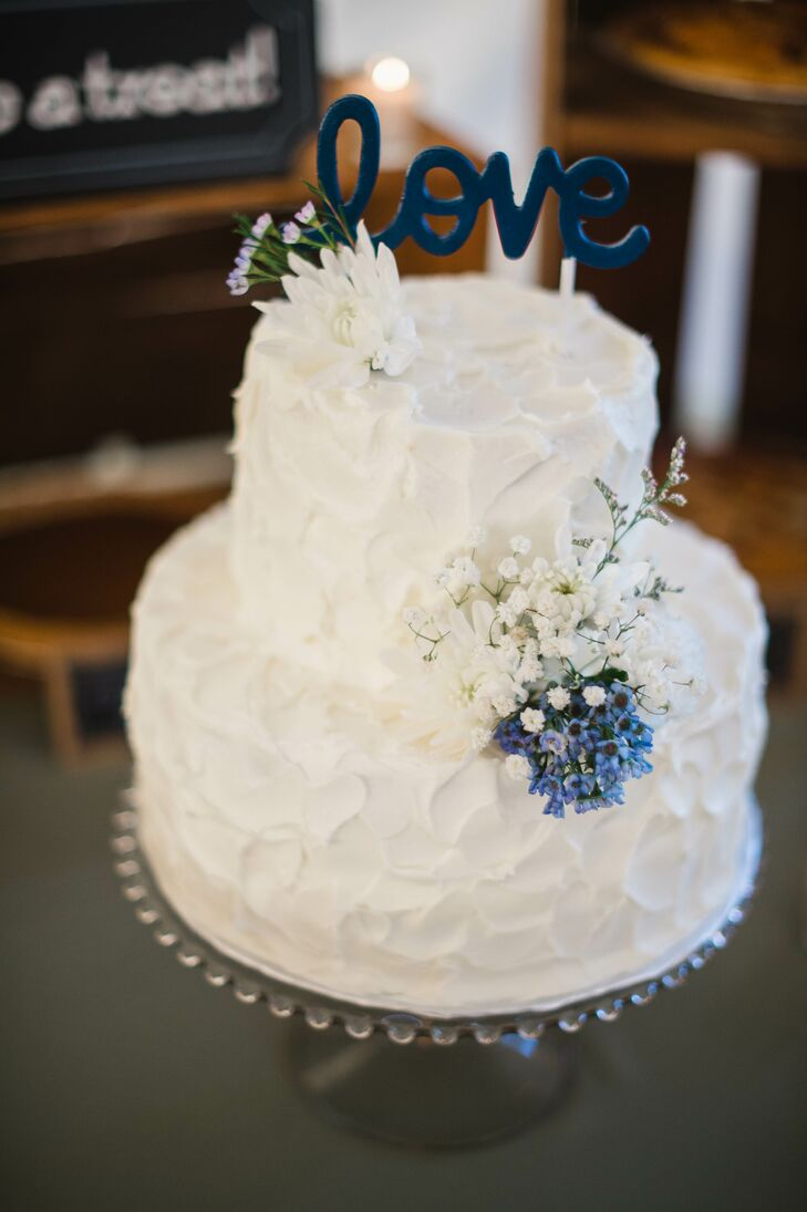 Allison and Matthew enjoyed a two-tier white textured buttercream cake decorated with baby's breath, dahlias and blue wildflowers.