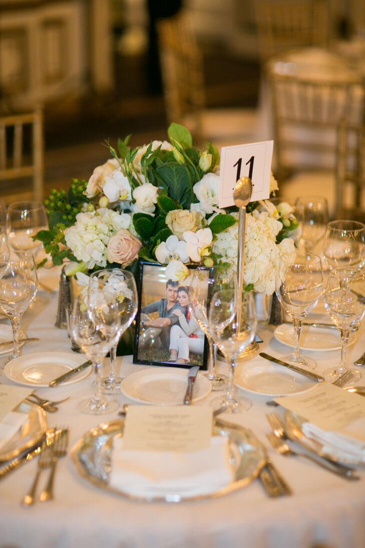 Lush flower centerpieces were made of hydrangeas, roses and orchids accented with green leaves. A white table number was held up with a gold holder, positioned next to a framed engagement photo of the couple.