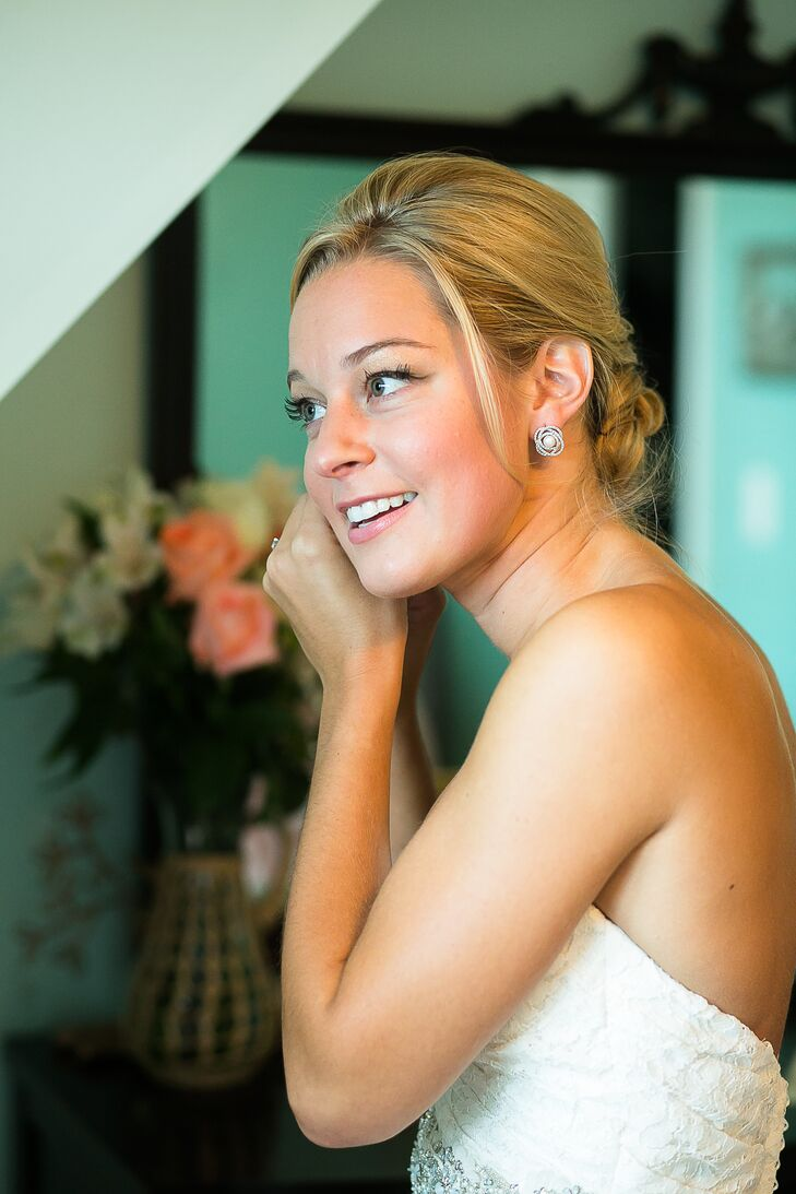 With a little help from the team at Head Games, Caitlin wore her hair in a classic updo with a few loose strands for a romantic touch. It was just the right fit for her all-lace white wedding dress by Mikaella Bridal. She finished off the look with bold pearl earrings surrounded by a fun curved halo design and simple espadrilles with white bows.