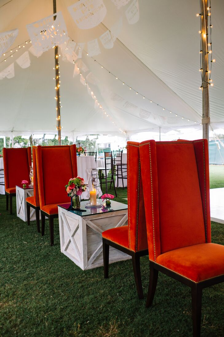 Guests had more than just their assigned chiavari chairs to lounge in during the reception. Caroline and Christopher set up a seating area with tall orange velvet chairs and wooden tables, so guests could chat and get a front-seat view of their friends on the dance floor.